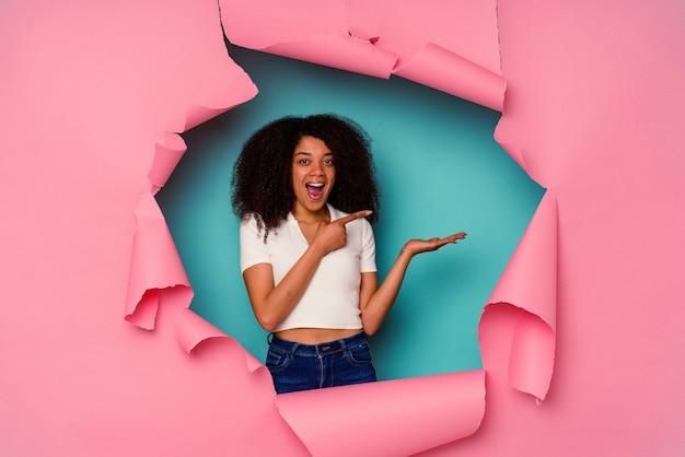 Jeune femme afro-américaine en papier déchiré isolé sur fond bleu excité tenant un espace de copie sur la paume.