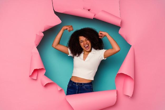 Jeune femme afro-américaine en papier déchiré isolé sur fond bleu montrant un geste de force avec les bras, symbole du pouvoir féminin