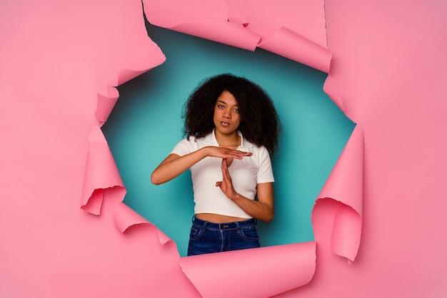 Jeune femme afro-américaine en papier déchiré isolé sur fond bleu montrant un geste de temporisation.
