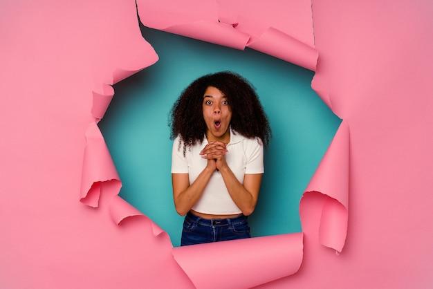 Jeune femme afro-américaine en papier déchiré isolé sur fond bleu priant pour la chance, étonné et ouvrant la bouche à l'avant.