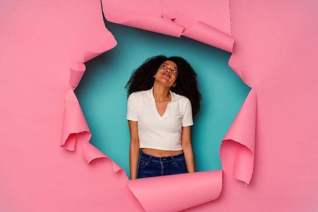 Jeune femme afro-américaine en papier déchiré isolé sur fond bleu rêvant d'atteindre des objectifs et des buts