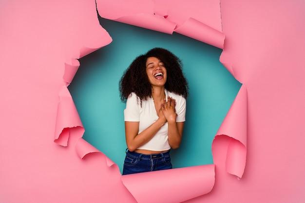 Jeune femme afro-américaine en papier déchiré isolé sur fond bleu en riant en gardant les mains sur le cœur, concept de bonheur.