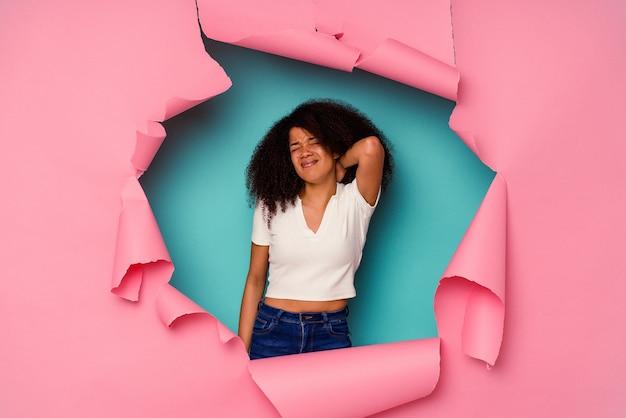 Jeune femme afro-américaine en papier déchiré isolé sur fond bleu souffrant de douleurs au cou en raison d'un mode de vie sédentaire.
