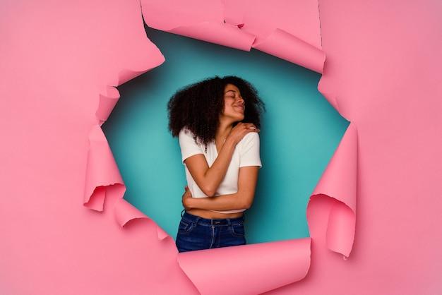 Jeune femme afro-américaine en papier déchiré isolée sur des câlins bleus, souriante insouciante et heureuse.