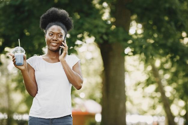 Une jeune femme afro-américaine parlant à un téléphone dans le parc
