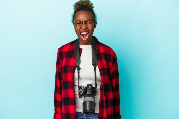 Jeune femme afro-américaine photographe isolée sur fond bleu criant très en colère et agressive.