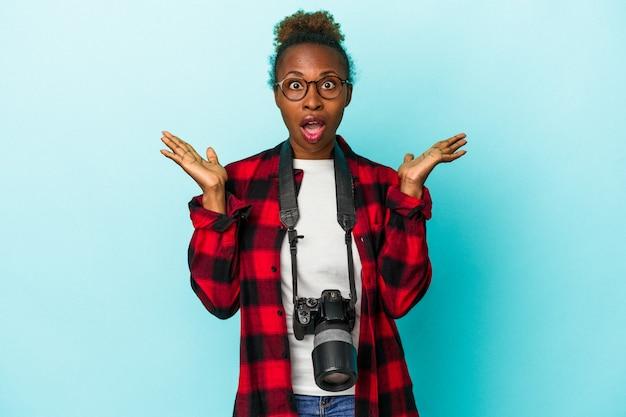 Jeune femme afro-américaine photographe isolée sur fond bleu surpris et choqué.