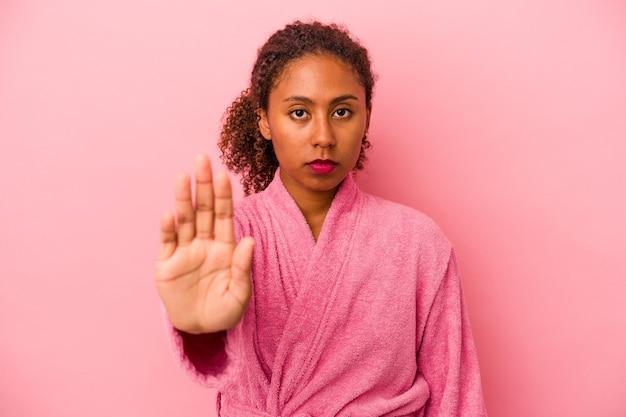 Jeune femme afro-américaine portant un peignoir isolé sur fond rose debout avec la main tendue montrant un panneau d'arrêt, vous empêchant.