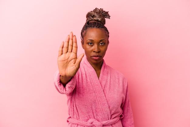Jeune femme afro-américaine portant un peignoir rose isolé sur fond rose debout avec la main tendue montrant un panneau d'arrêt, vous empêchant.