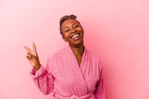 Jeune femme afro-américaine portant un peignoir rose isolé sur fond rose joyeux et insouciant montrant un symbole de paix avec les doigts.