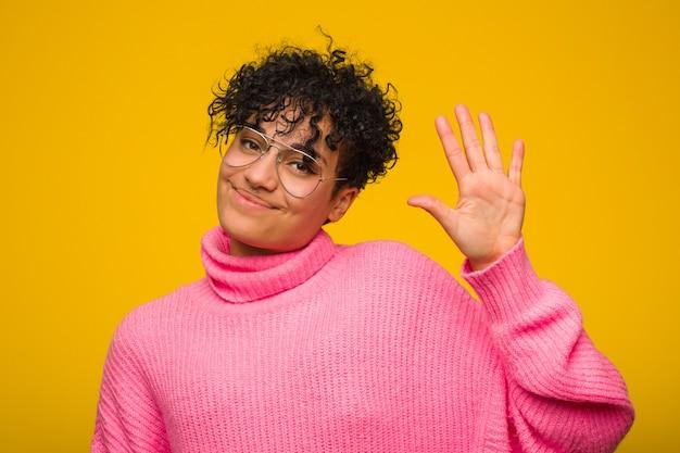 Jeune femme afro-américaine portant un pull rose souriant joyeux montrant le numéro cinq avec les doigts.