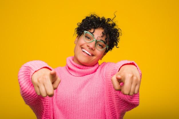 Jeune femme afro-américaine portant un pull rose sourires joyeux pointant vers l'avant.