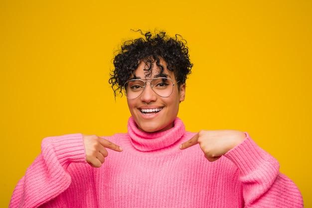 Jeune femme afro-américaine portant un pull rose surpris en pointant avec le doigt, souriant largement.