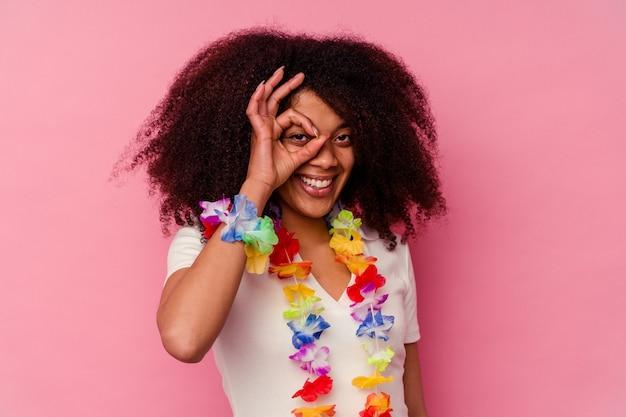 Jeune femme afro-américaine portant un truc hawaïen excité en gardant un geste correct sur les yeux.
