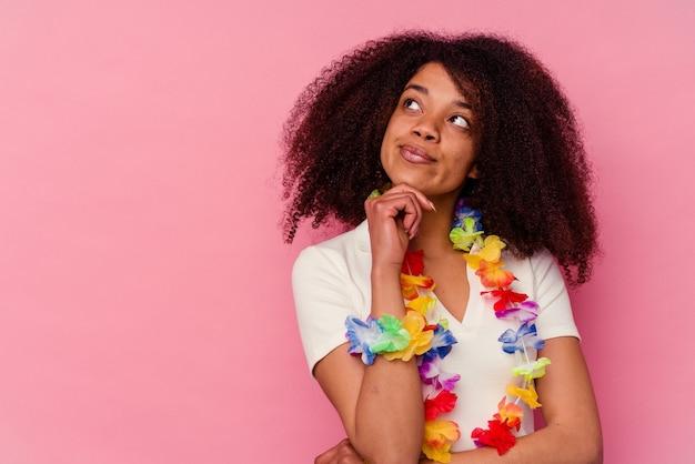 Jeune femme afro-américaine portant un truc hawaïen regardant de côté avec une expression douteuse et sceptique.