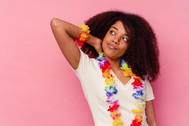 Jeune femme afro-américaine portant un truc hawaïen touchant l'arrière de la tête, pensant et faisant un choix.