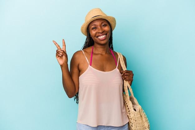 Jeune femme afro-américaine portant des vêtements d'été isolés sur fond bleu joyeux et insouciant montrant un symbole de paix avec les doigts.
