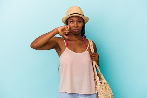 Jeune femme afro-américaine portant des vêtements d'été isolés sur fond bleu montrant un geste d'aversion, les pouces vers le bas. notion de désaccord.