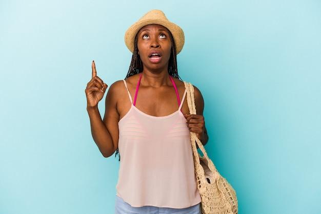 Jeune femme afro-américaine portant des vêtements d'été isolés sur fond bleu pointant vers le haut avec la bouche ouverte.