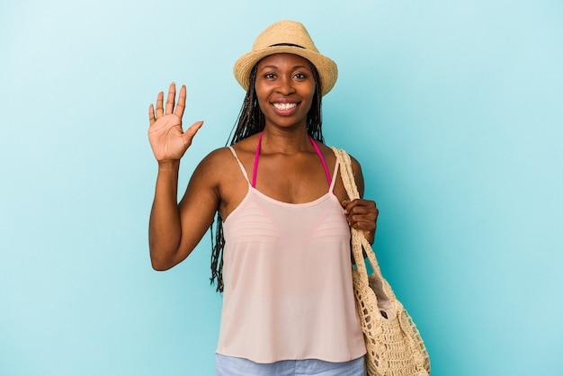 Jeune femme afro-américaine portant des vêtements d'été isolés sur fond bleu souriant joyeux montrant le numéro cinq avec les doigts.