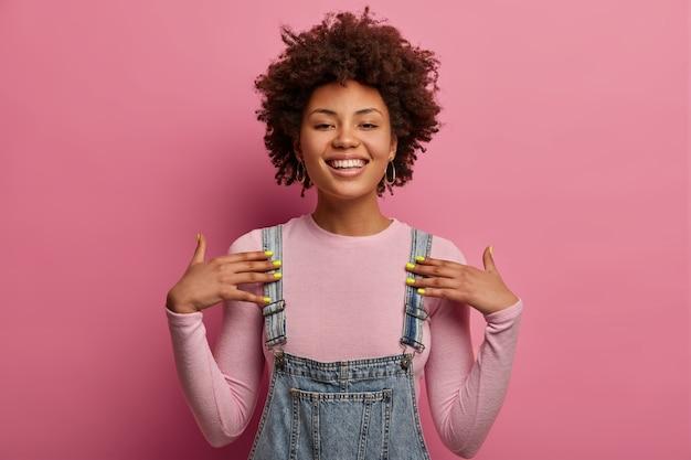Une jeune femme afro-américaine positive se montre, se sent fière, sourit largement, étant de grande humeur, habillée de vêtements décontractés, pose contre un mur rose pastel, a une expression confiante