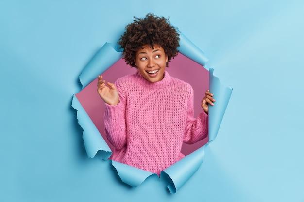 Jeune femme afro-américaine positive sourit joyeusement garde la main levée a une expression insouciante