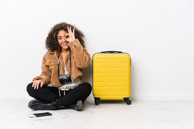 Jeune femme afro-américaine prête pour un voyage excité en gardant le geste ok sur les yeux.