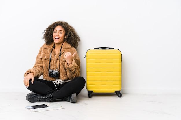 Jeune femme afro-américaine prête pour un voyage points avec le pouce, riant et insouciant.