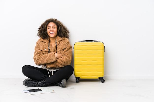Jeune femme afro-américaine prête pour un voyage en riant et en s'amusant.