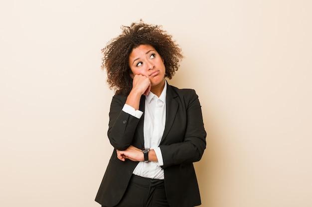 Jeune femme afro-américaine qui se sent triste et pensif, regardant l'espace copie.