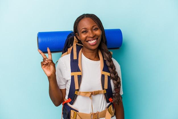 Jeune femme afro-américaine de randonnée isolée sur fond bleu joyeuse et insouciante montrant un symbole de paix avec les doigts.