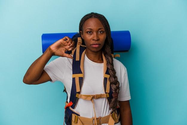 Jeune femme afro-américaine de randonneur isolée sur fond bleu montrant un geste d'aversion, les pouces vers le bas. notion de désaccord.