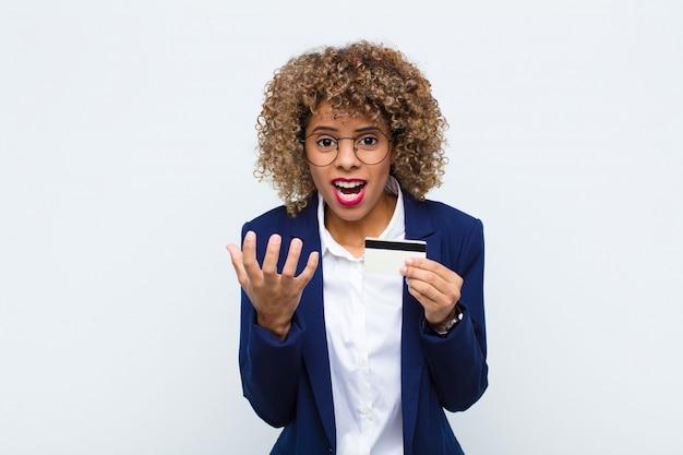 Jeune femme afro-américaine à la recherche désespérée et frustrée, stressée, malheureuse et ennuyée, criant et criant avec une carte de crédit