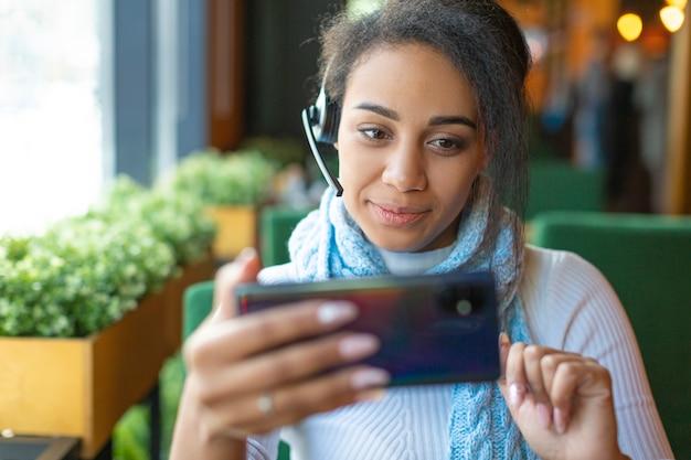 Jeune femme afro-américaine regarde de près l'écran d'un téléphone mobile lors d'un en ligne