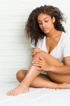 Jeune femme afro-américaine se crème hydratante sur les jambes