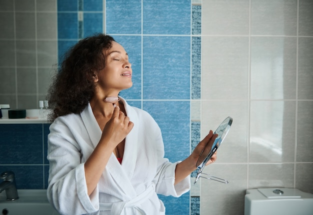 Jeune femme afro-américaine se relaxant pendant le lissage du cou et le massage du drainage lymphatique avec un masseur à rouleaux en pierre de jade