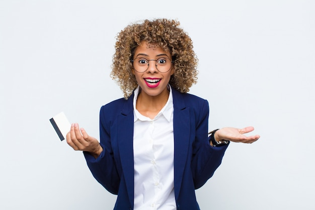 Jeune femme afro-américaine se sentant perplexe et confus, doutant, pondérant ou choisissant différentes options avec une drôle d'expression avec une carte de crédit