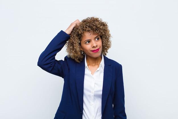 Jeune femme afro-américaine se sentant perplexe et confus, se grattant la tête et regardant sur le côté sur un mur plat