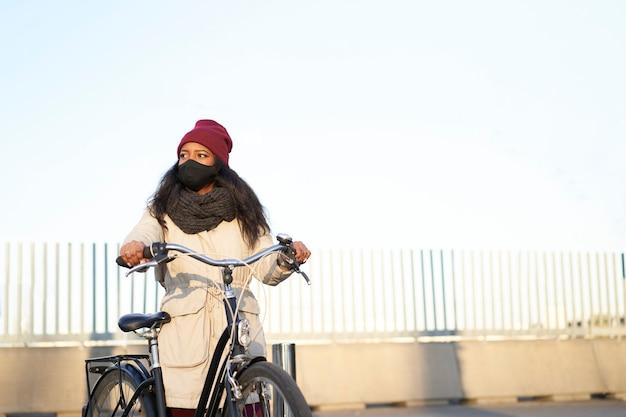 Jeune femme afro-américaine sur son vélo, portant des vêtements d'hiver. fond propre avec espace de copie.
