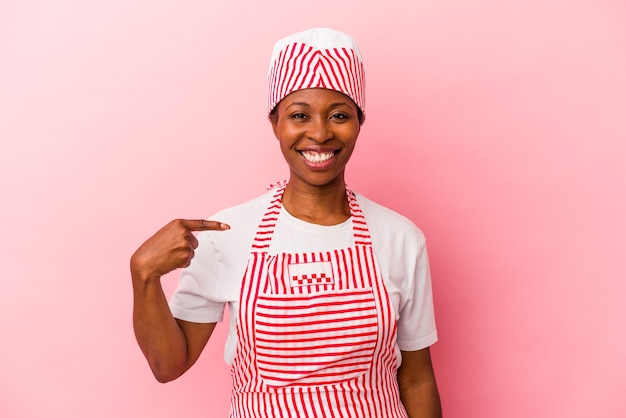 Jeune femme afro-américaine de sorbetière isolée sur fond rose personne pointant à la main vers un espace de copie de chemise, fière et confiante
