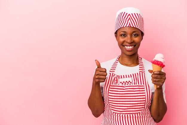 Jeune femme afro-américaine de sorbetière tenant une crème glacée isolée sur fond rose souriant et levant le pouce vers le haut