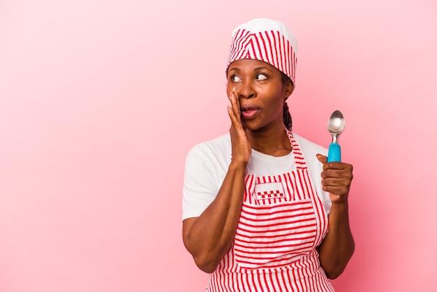 Jeune femme afro-américaine sorbetière tenant une cuillère isolée sur fond rose dit une nouvelle secrète de freinage à chaud et regarde de côté
