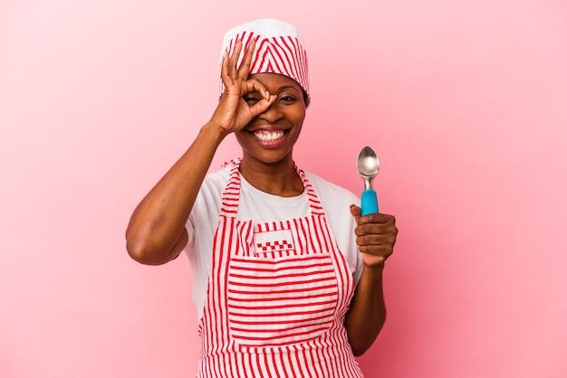 Jeune femme afro-américaine de sorbetière tenant une cuillère isolée sur fond rose excitée en gardant le geste ok sur les yeux.