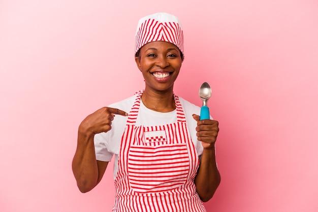 Jeune femme afro-américaine sorbetière tenant une cuillère isolée sur fond rose personne pointant à la main vers un espace de copie de chemise, fière et confiante