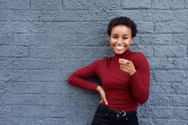 Jeune femme afro-américaine, souriant et en pointant le doigt