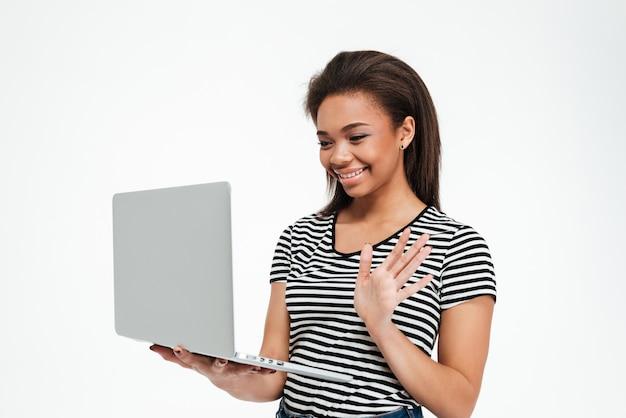 Jeune femme afro-américaine souriante, agitant la main à l'ordinateur portable