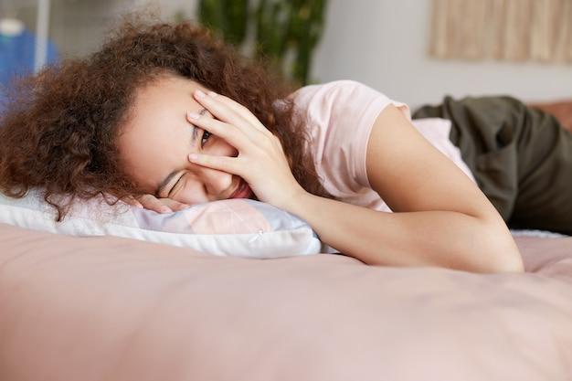 Jeune femme afro-américaine souriante allongée sur le lit et face à face avec la main, profiter de la journée ensoleillée à la maison et a l'air heureux.