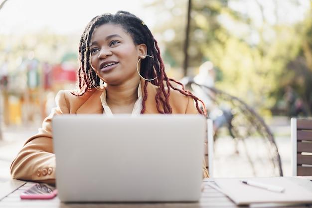 Jeune femme afro-américaine souriante assise à la table dans un café de la rue et utilisant un ordinateur portable