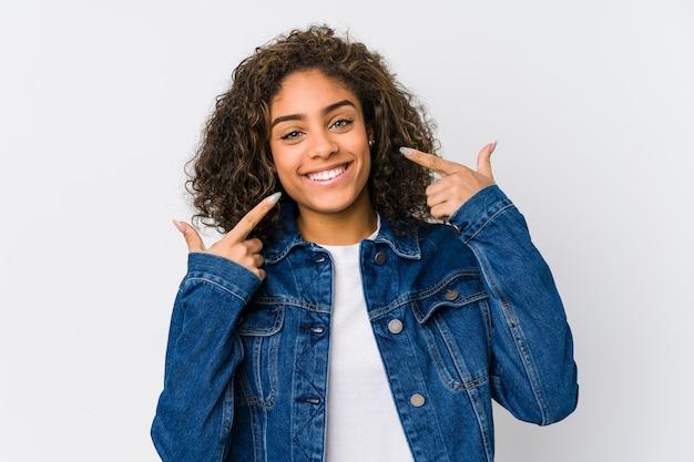 Jeune femme afro-américaine sourit, pointant les doigts sur la bouche.