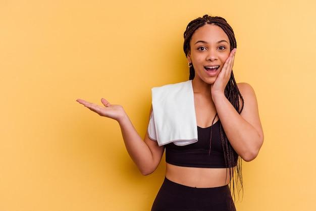 Jeune femme afro-américaine de sport tenant une serviette isolée sur fond jaune détient un espace de copie sur une paume, gardez la main sur la joue. émerveillé et ravi.